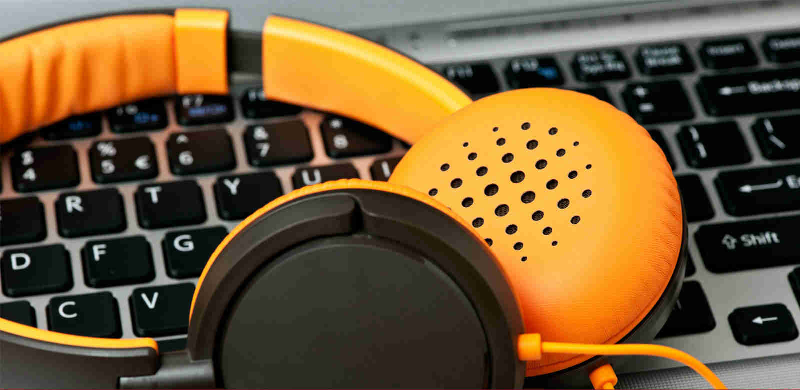 A pair of orange headphones resting on a laptop keyboard